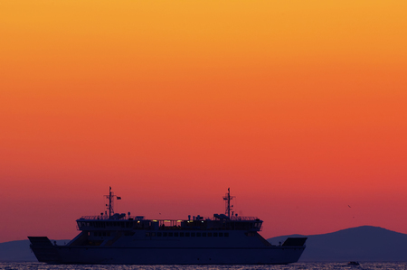 Silhouette of a ferry on radiant sunset background