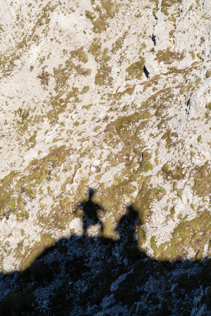 Shadow of two mountaineers at the top of the mountain on the surface of rocky slope covered with patches of grass and moss