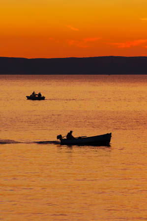 Silhouettes of fishermen in boats returning home after sunset