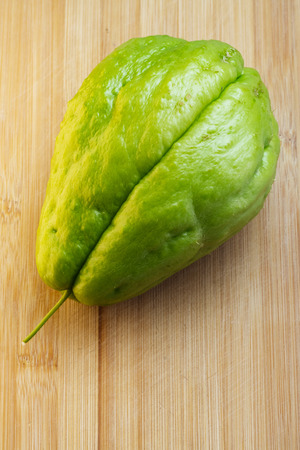 Fresh green Chayote on cutting board made of bamboo wood, viewed from above Foto de archivo - 116229551