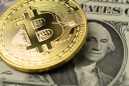 Golden Bitcoin cryptocurrency coin covering the image of George Washington on one US Dollar banknote