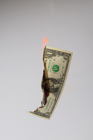 Burning one US Dollar banknote isolated on grey background with visible flame Stok Fotoğraf