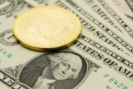 Closeup of one US Dollar banknote with Bitcoin cryptocurrency coin on top