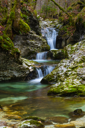 Silky cascades of fresh turquoise mountain stream in autumn forest