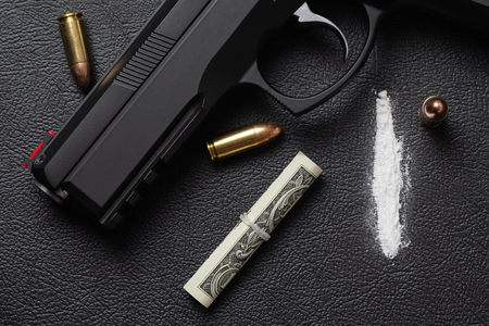 Dollar bill scroll, line of cocaine powder, 9 mm pistol and three full metal jacket bullets on black surface. Conceptual mockup of illegal drug dealing, criminal, trafficking or war on drugs. 免版税图像 - 116179169