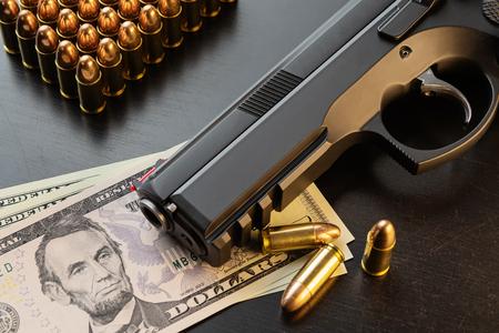 Pistolet semi-automatique de 9 mm et balles entièrement en métal sur des billets en dollars disposés sur un tableau noir. Maquette conceptuelle du contrôle des armes à feu, du crime, du complexe militaro-industriel ou de la défense.