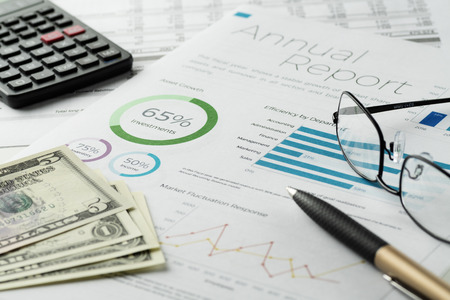 Mockup financial charts report sheet with visible pen, calculator, eyeglasses and dollar banknotes. Accounting, business, finance, tax and office concepts.