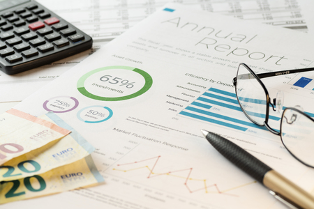 Mockup financial charts report sheet with visible pen, calculator, eyeglasses and euro banknotes. Accounting, business, finance, tax and office concepts.