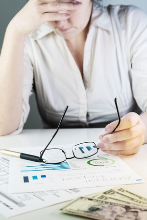 Business woman analysing financial charts, supporting her head with arm and holding eyeglasses. Visible pen and dollar banknotes on white desk. Accounting, business, finance, tax and office concepts. Stock fotó