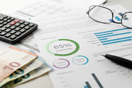 Mockup investment financial charts report sheet with visible pen, calculator, eyeglasses and euro banknotes. Accounting, business, finance, tax and office concepts.