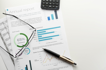 Mockup annual report sheet with charts and graphs, pen, calculator and eyeglasses on white desk. Accounting, business, finance, tax and office concepts with copyspace. Archivio Fotografico