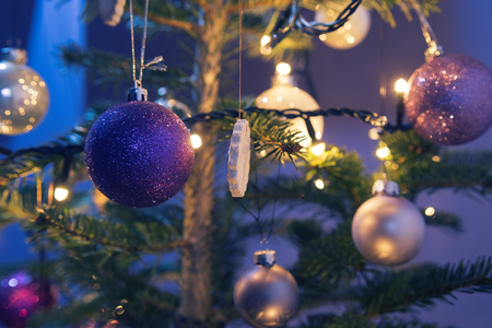 Closeup Of Christmas Ornaments On Real Christmas Tree And Purple