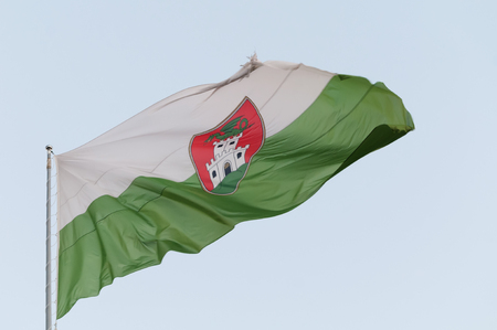 Closeup of weathered and torn flag of the city of Ljubljana waving in the wind. White-green flag with red emblem on the flagpole with bluish sky background. Capital of Slovenia.
