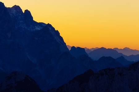 Layers of high peaks of Julian Alps in Italy with bright orange sunset sky in background. Hiking, mountaineering, travel and environment concepts. Stock Photo