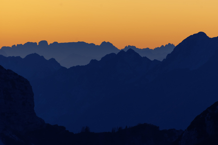 Silhouette of layers of alpine mountain ranges in Italy with bright orange sunset sky in background. Hiking, mountaineering, travel and environment concepts. Stock Photo