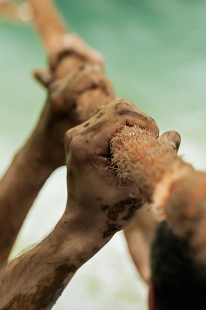 Closeup of dirty hands hanging on tight to the climbing rope. Boot camp, military training, climbing and competition concepts. Фото со стока