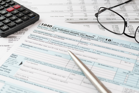 U.S. Individual Income Tax Return form 1040 with pen, calculator and eyeglasses. Tax, accounting, business, finance and office concepts. Stockfoto