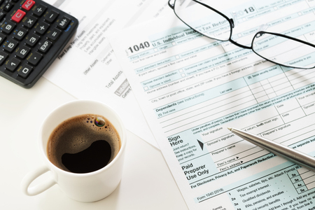 White cup of black coffee espresso on white table with visible U.S. Individual Income Tax Return form 1040, pen, calculator and eyeglasses. Tax, accounting, business, finance and office concepts.