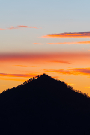 Silhouette of pyramid shaped mountain and vividly colored evening sky in the background. Hiking, mountaineering, magical nature and environment concepts.