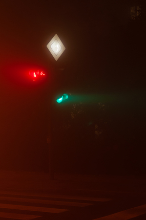 Green traffic light and dont walk red light on lighting pole at crossroad in dense fog. Traffic, safety, traffic accident and visibility concepts.