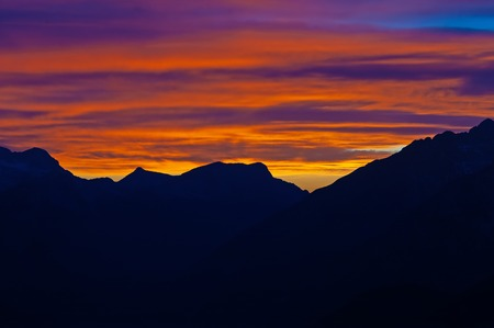 Magical twilight sky panorama after sunset and silhouette of alpine mountain ranges in foreground. Hiking, mountaineering, magical nature and environment concepts.