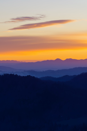 Beautifully colored layers of hills and sky in twilight colors after sunset. Hiking, mountaineering, magical nature and environment concepts.