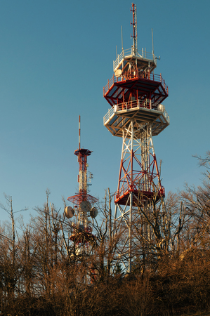 Two red and white telecommunications towers with satellite dishes and cellular antennas on top of the hill and blue sky background. Telecommunication, telephone and television concepts. 4G, LTE, 5G Stock Photo