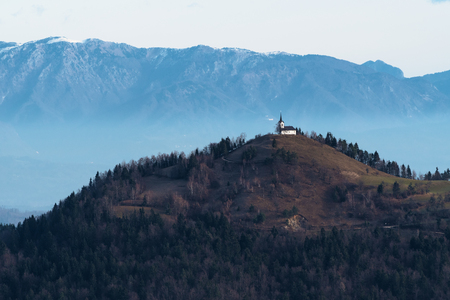 St. Jacob church on top of the hill in the dull colors of winter in Slovenia. Religion, hiking, travel and nature concepts. Stock Photo
