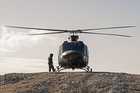 Pilot checking military helicopter before taking off from helipad on top of mountain. Military, airforce, defense and mountain rescue concepts.