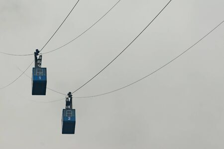 Two cable cars in foggy weather carrying passengers to nearby mountain. Transportation, aerial lift, skiing and weather concepts