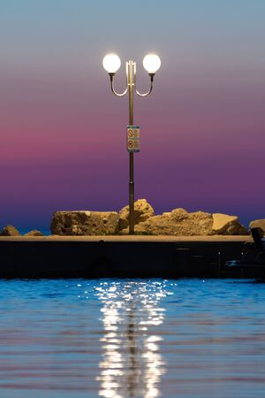 Lit lamppost with no nudism and no dogs allowed sign on pier after sunset with magically colored twilight sky in background. Vacation, summer and turism concepts. Stock Photo