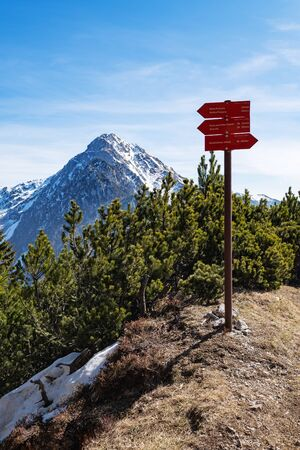Red signpost on mountain top indicating nearby hiking destinations, time and elevation in Slovenian Alps. Hiking, backpacking, mountaineering, achievement, lifestyle and nature concepts.