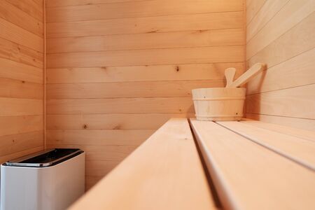 Details from a small private Finnish sauna. Wooden bucket with scoop on bench and heater. Wellbeing, health, detoxification and luxury concepts