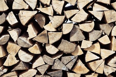 Closeup of neatly stacked pile of cut and split spruce tree firewood. Forestry, renewable fuel, sustainability and environment concepts.