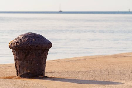 Old and rusty mooring bollard on concrete pier with blue sea with sailboat on horizon. Sailing, vacation, travel, tourism and maritime activities concepts