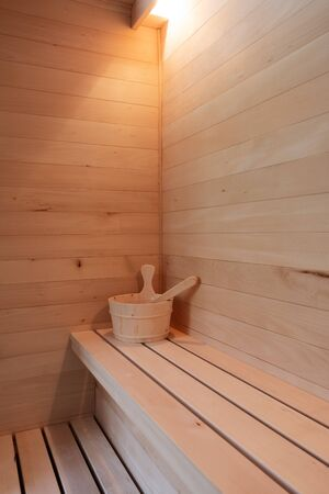 Details from a small private Finnish sauna. Wooden bucket with scoop on bench. Wellbeing, health, detoxification and luxury concepts 版權商用圖片