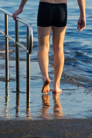 Male swimmer visible from waist down walking barefoot toward the sea holding the pier fence at sunset. Swimming, summer and vacation concepts