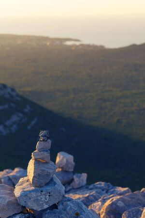 Stack of rocks on top of the Scah mountain overlooking the bay of Ugljan island in Croatia at sunset. Hiking, wilderness, direction, waypoint concept background.