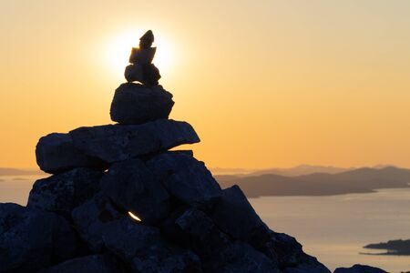 Silhouette of stack of rocks on top of the Scah mountain on the Ugljan island overlooking the nearby islands in Adriatic sea in Croatia at sunset. Hiking, vacation, direction and travel concepts. Stock Photo
