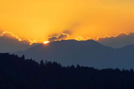 Radiant orange sky with sun setting behind mountain range and silhouette of spruce forest in foreground. Atmosphere, nature, forestry, climate change and environment concepts. 版權商用圖片