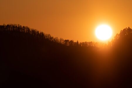 Orange sky with brightly glowing sun setting behind treelined hill. Atmosphere, nature, forestry, climate change and environment concepts.
