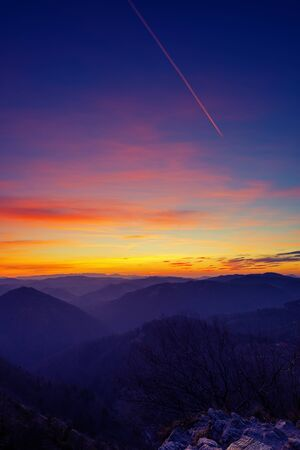 Beautiful intense and deep colors of twilight sky and landscape after sunset with purple trail from passing airplane. Hiking, colors in nature, air pollution and transportation concepts. Stock fotó