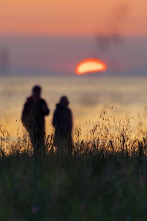 Silhouette of couple walking by the coast and watching the setting sun with tall grass in foreground. Vacations, emotions, seasons and environment concepts