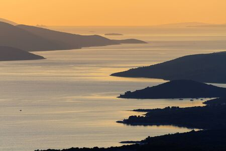 Aerial view of capes and bays of the island of Ugljan in Croatian Adriatic sea during sunset with nearby islands visible in background. Travel, tourism, sea and summer vacation concepts.
