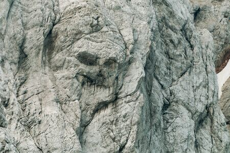 Gray mountain wall resembling a pirate skull face in Slovenian Alps. Alpinism, mountain climbing, traversing, natural features and symbolism concepts 写真素材