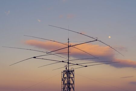 Array of telecommunication antennas on steel tower with moon and twilight sky in background. Telecommunication, telephone, ham radio and television concepts. 4G, LTE, 5G