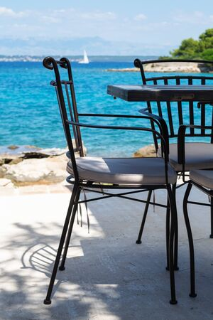 Vacant chair and table at the bar next to the beach on Croatian island Ugljan. Summer, vacation, travel, luxury and relaxation concepts.