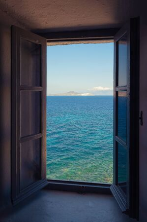 Beautiful view of turquoise colored sea and island from an old window in Greece. Travel, tourism, ocean and summer vacation concepts. Banco de Imagens