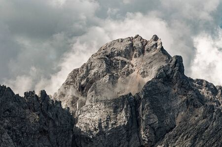 Mighty mountain in Slovenian Alps surrounded by dramatic clouds. Alpinism, mountain climbing, danger, geology and weather concepts 版權商用圖片
