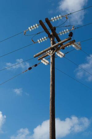 Old wooden three-phase electric utility pole with cables on a blue sky in background